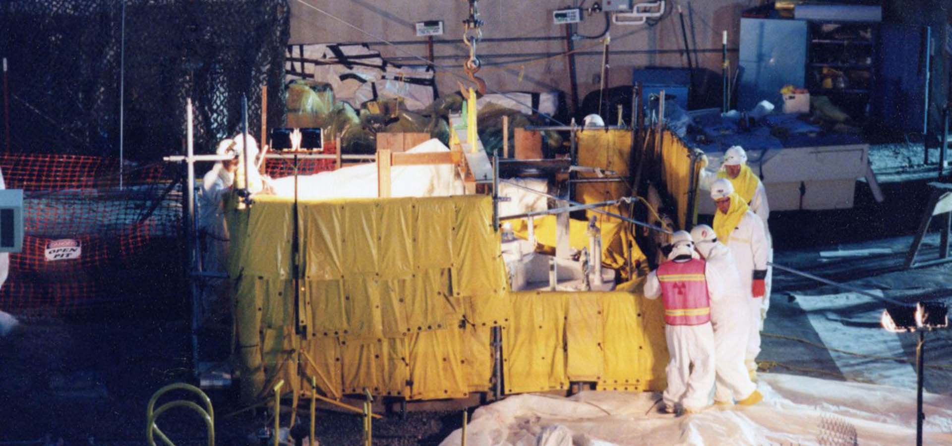 Workers in protective suits cleaning up a nuclear site.