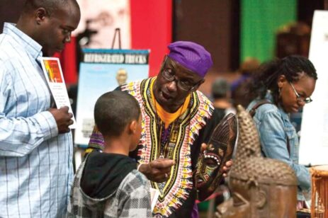 African-American man dressed in traditional African dress, speaking with a young boy.