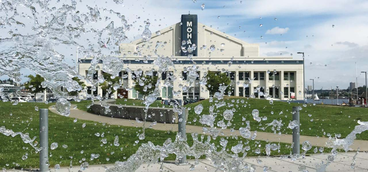 Photograph of MOHAI with water spray from a walkway fountain in the foreground.