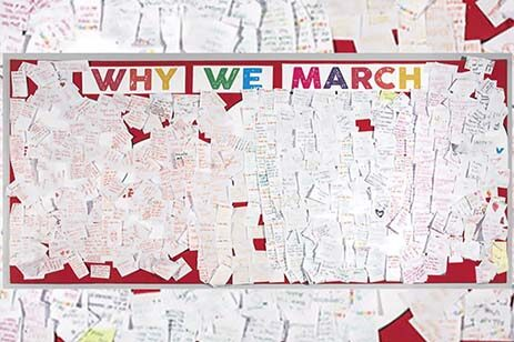 Bulletin board with hundreds of notes posted on it under a heading reading 'Why We March.