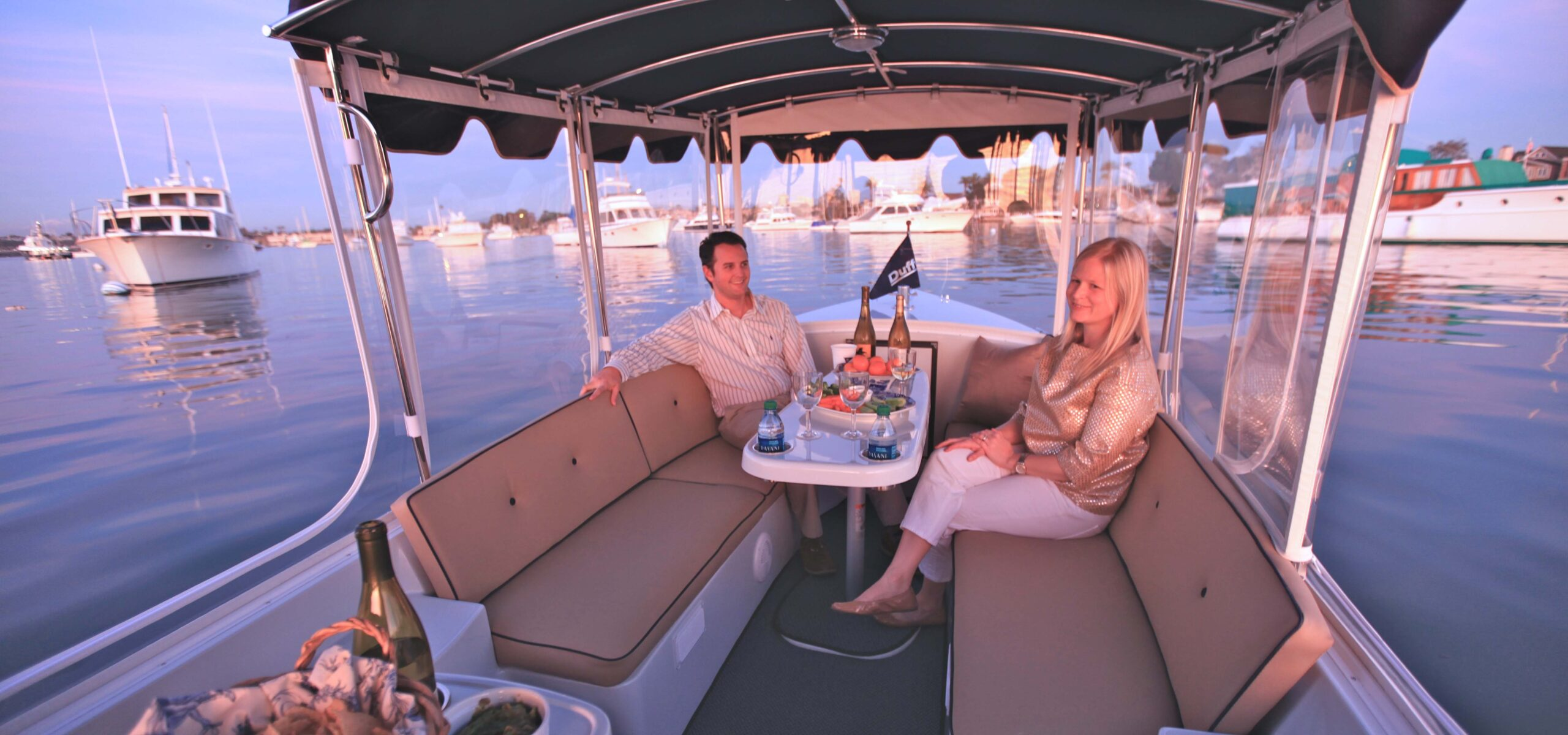 Two people enjoying a sunset picnic dinner on a Seattle Electric Boat rental.