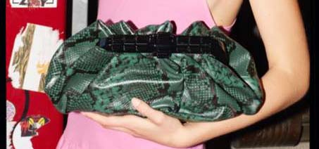 Green snake leather purse in the arms of a women wearing a pink dress.