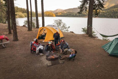 Family around a campfire by an orange tent pitched near a lake.