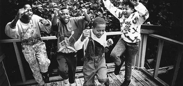 Black and white photo of four kids dancing.