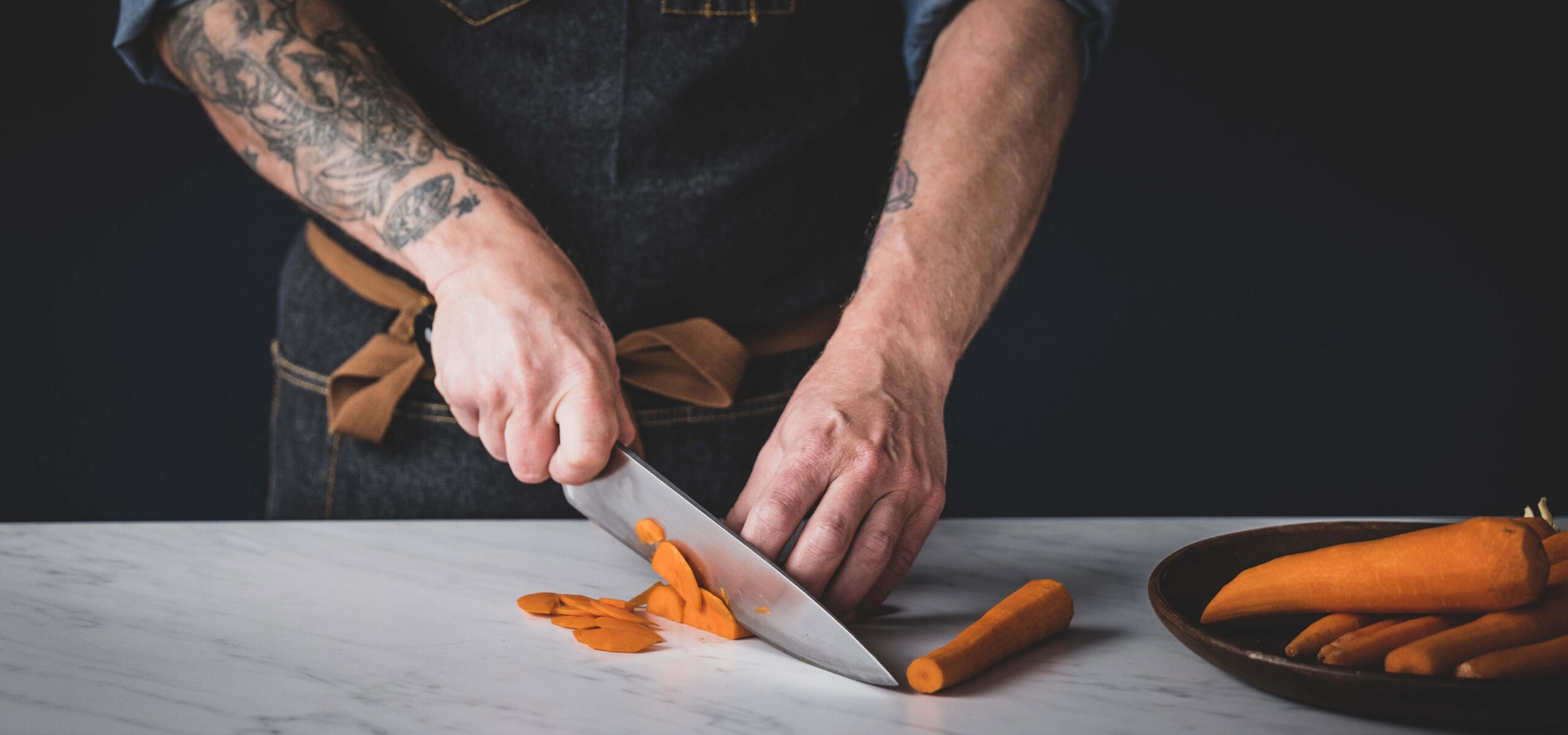Man with tattooed arms slicing a peeled carrot.
