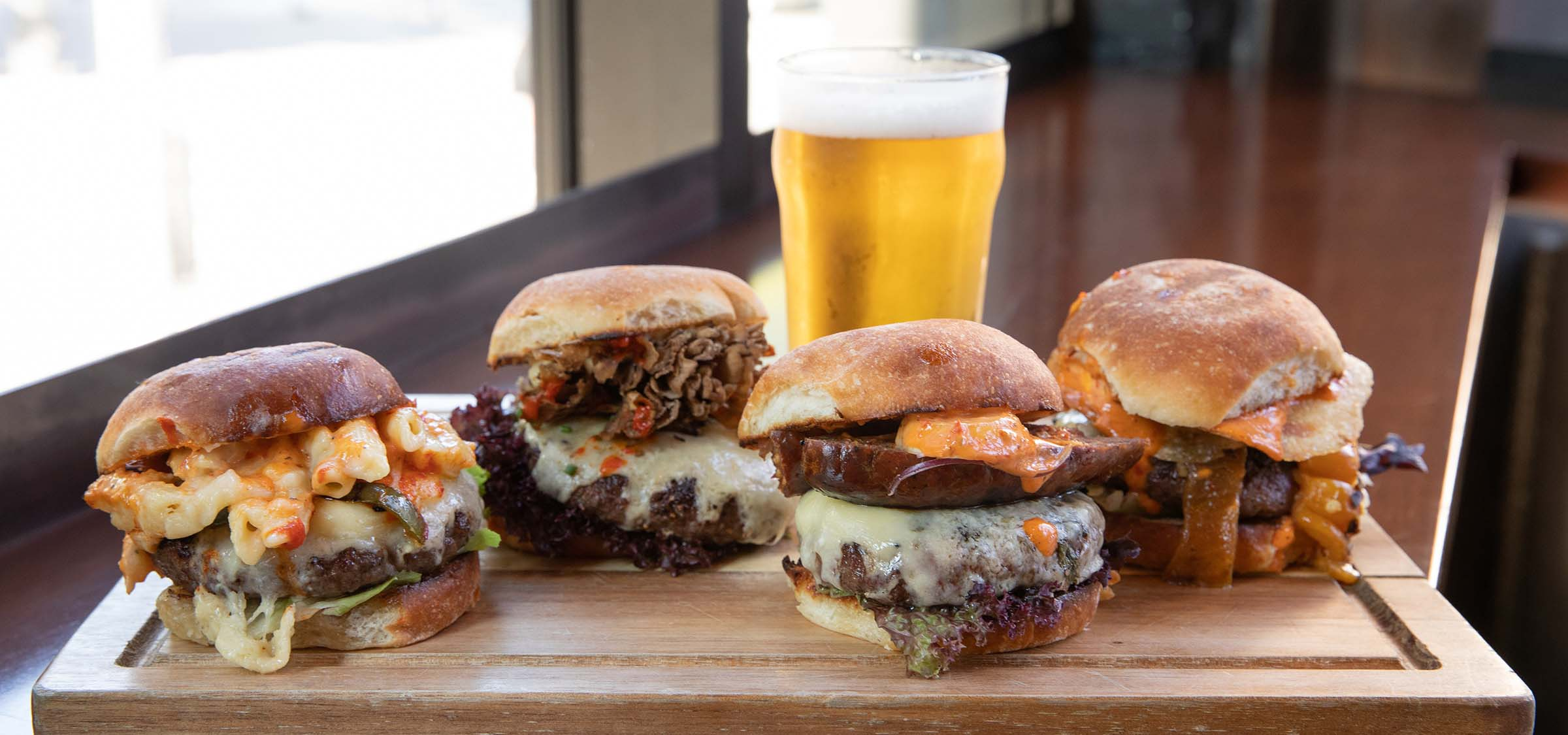 Wooden tray with four gourmet burgers and a beer in the background.