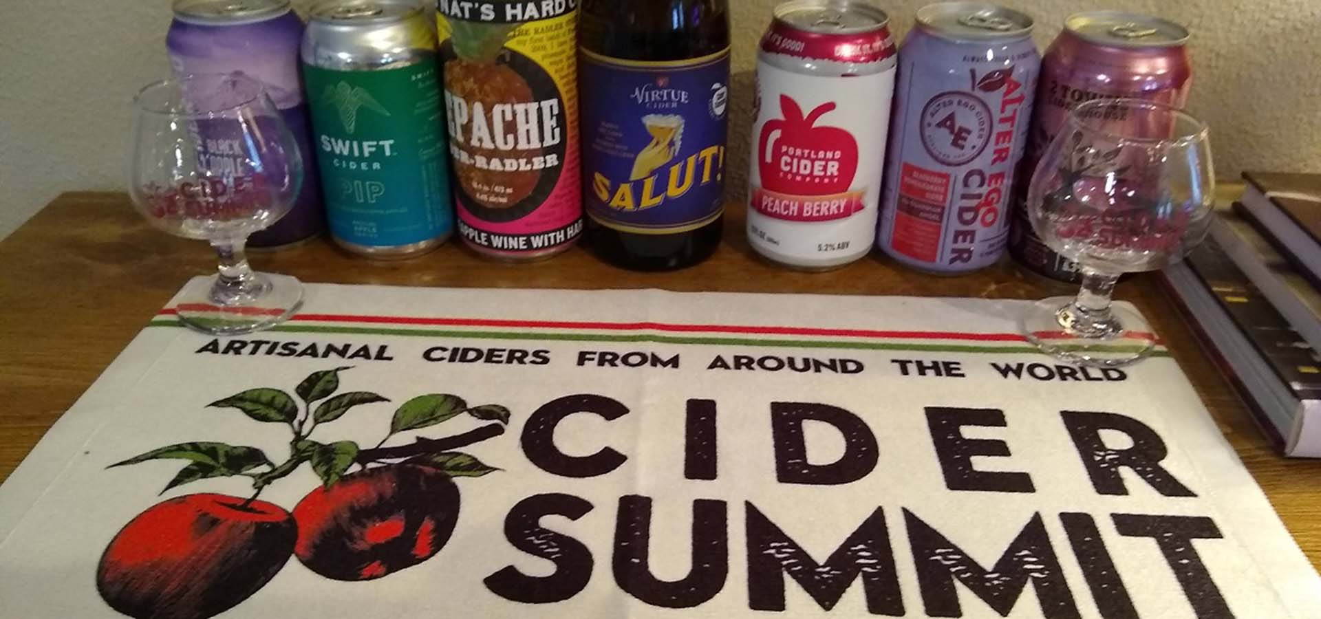 Seattle Cider Summit tasting kit offering; includes a bar towel with logo, 2 tasting glasses, and various ciders.