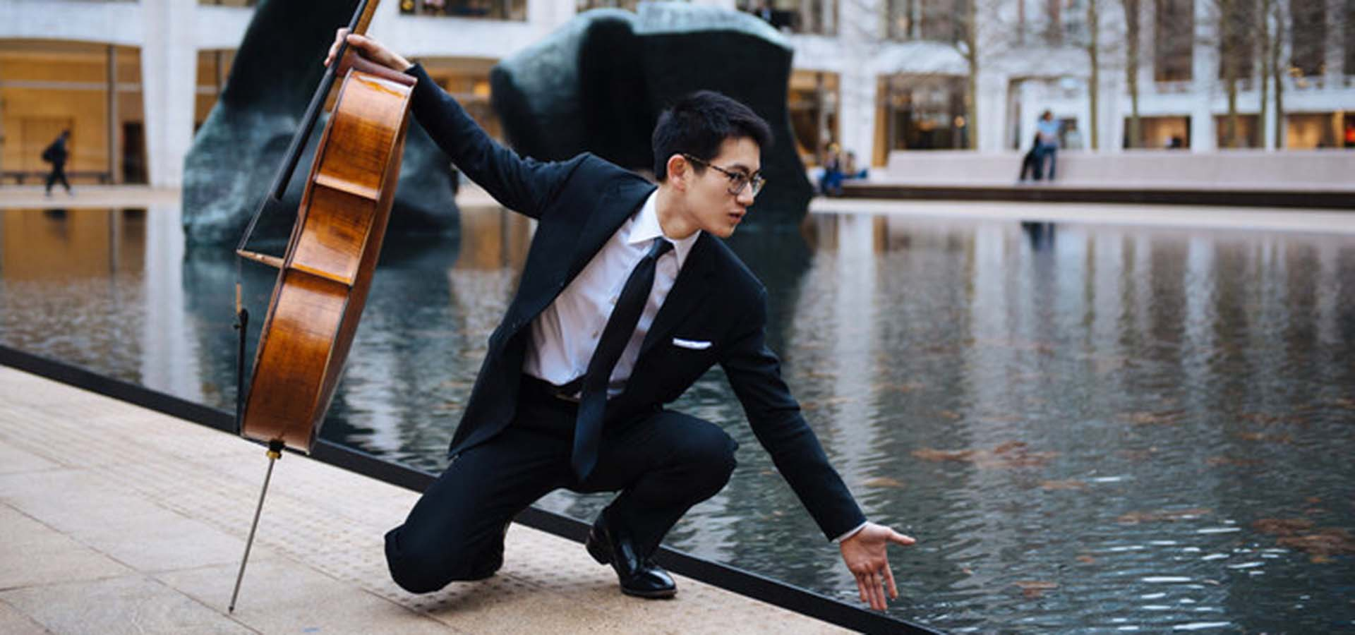 Cello playing touching a pool of water
