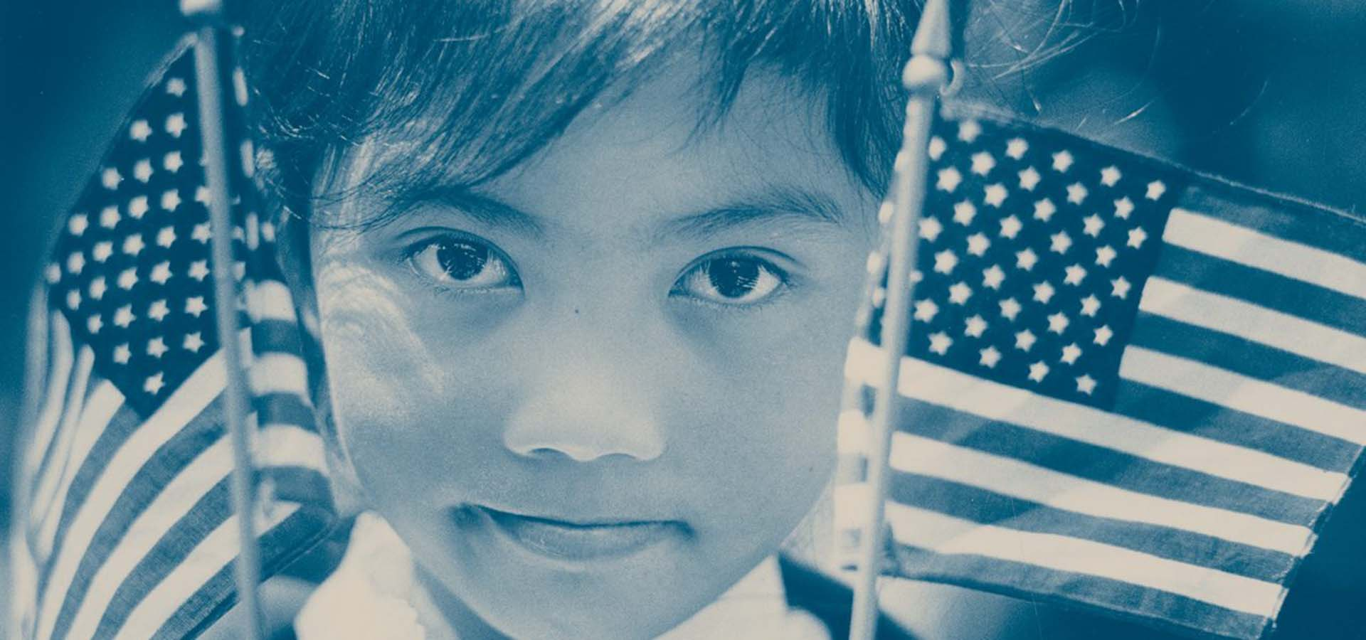 Blue tone photography of a minority child holding American flags.