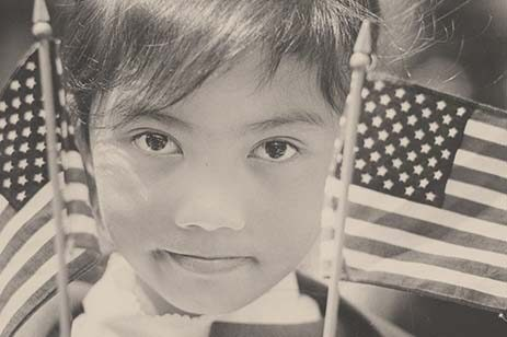 Young girl holding American flags