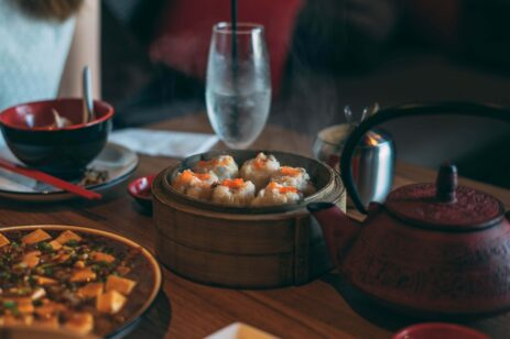 Steamer with dumplings on a table with a tea pot.