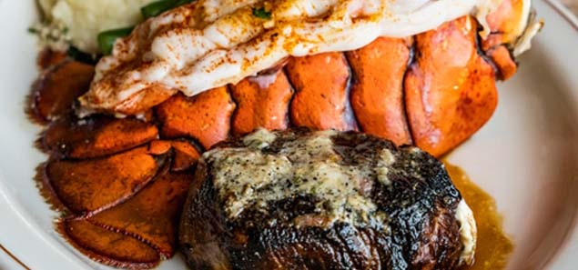 Steak filet and lobster tail dinner on a white plate.