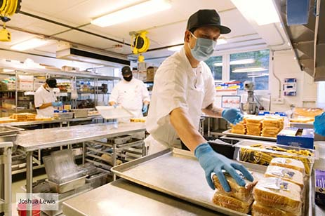 Food service worker making sandwiches wearing a face mask