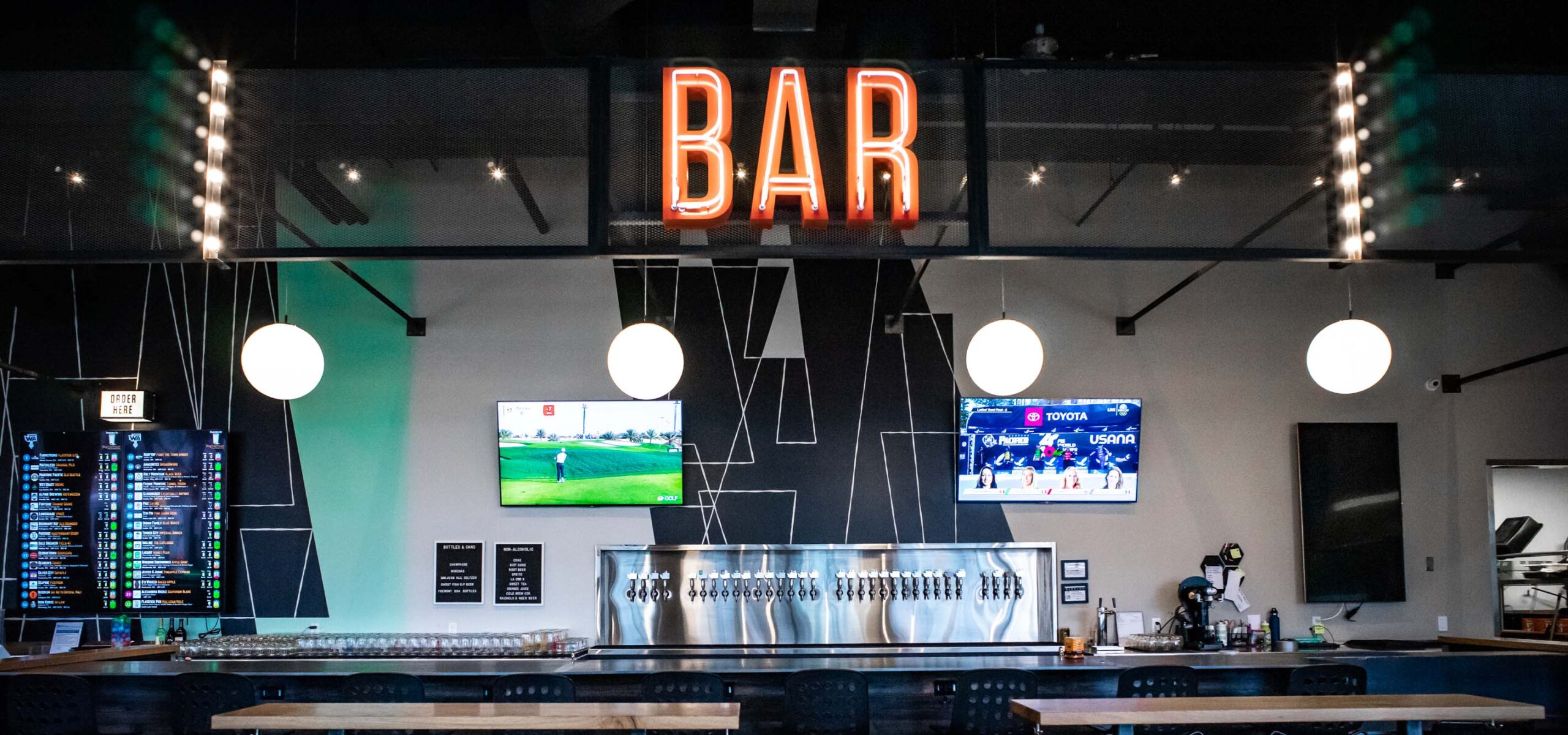 Bar counter with neon sign and TV screens above the bar.