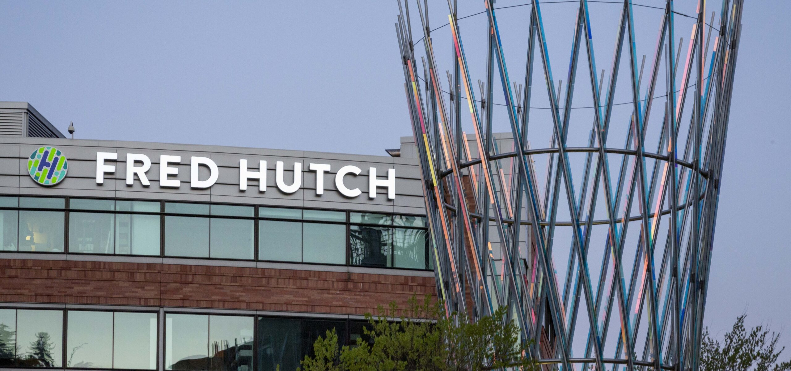View of the neon marquee sign of the Fred Hutch campus with some woven metal outdoor art sculpture in the foreground.