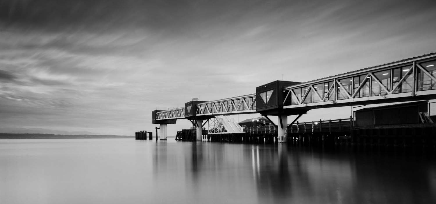 Black and white photo of an elevated tunnel over a body of water.