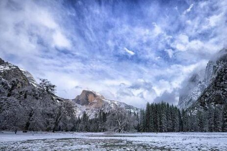 Mountain landscape photograph with snow covered mountains and blue sky.