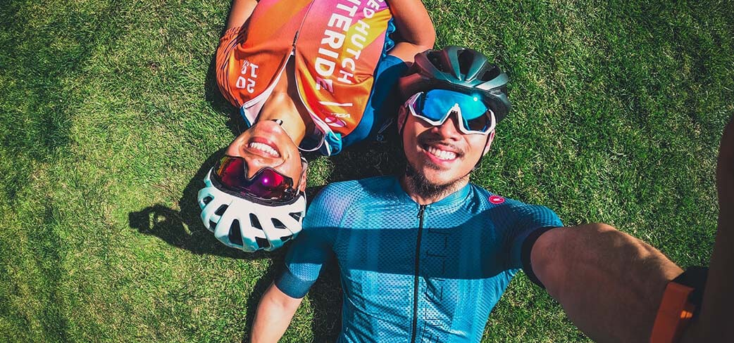 Couple of cyclist resting by lying down in some grass.