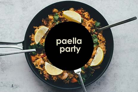 Paella in a pan with lemons on top.