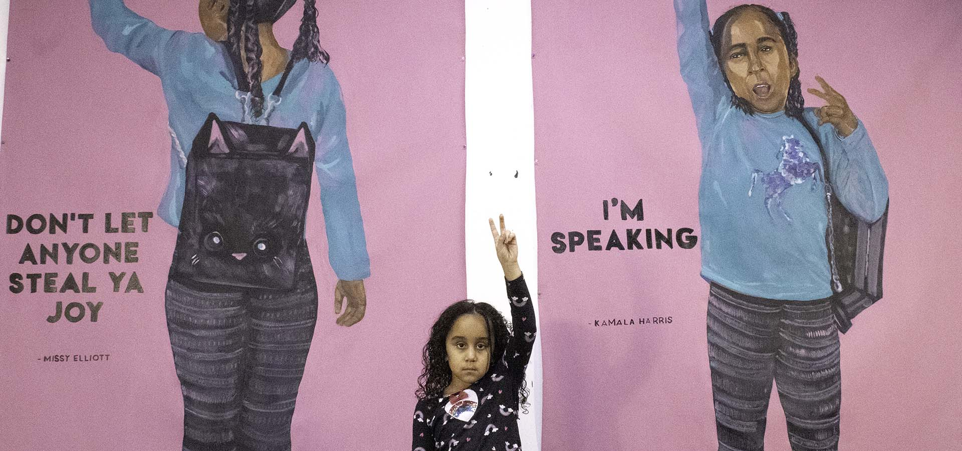 Window mural art featuring an African-American girl with messaging about BIPOC awareness with young girl in front holding up a peace sign with her fingers.