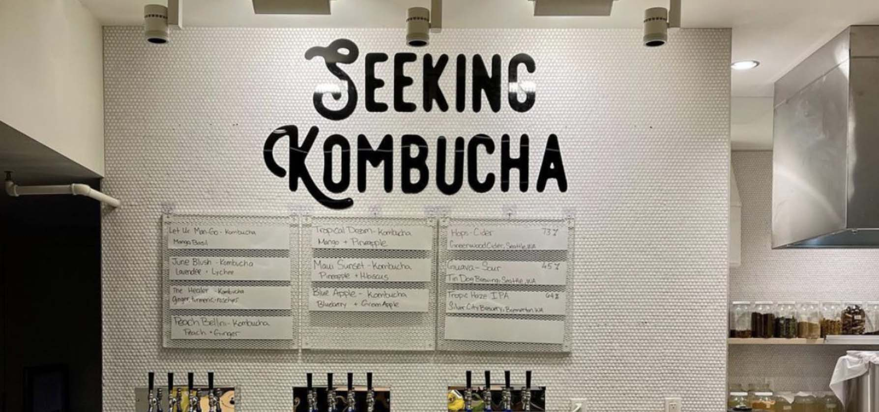 Inside a kombucha shop with menu on the wall and taps on behind the counter.