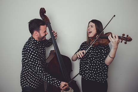 A man and women playing a cello and violin