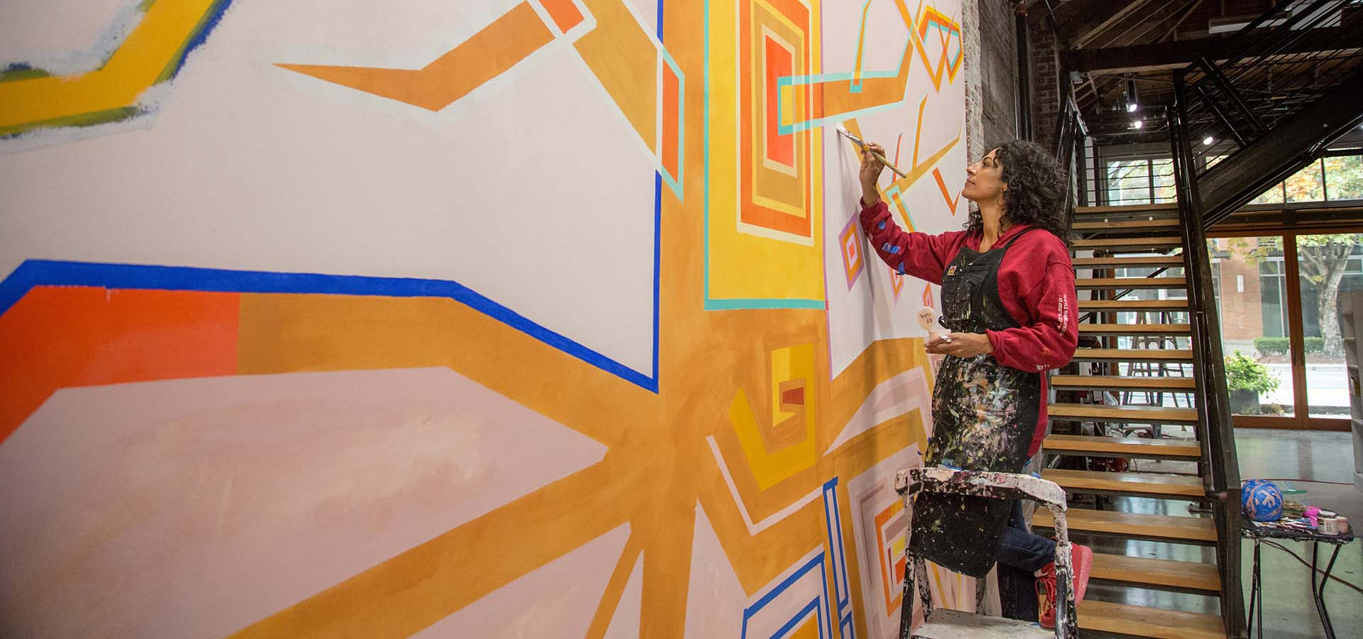 Artist Marela Zacarías working on a painting with vibrant colors.