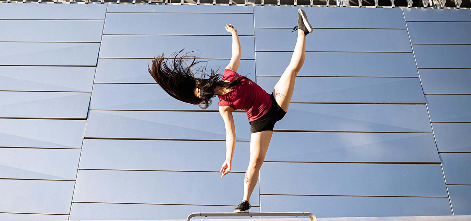 Female dancer balancing on a rail outside a mirrored building.