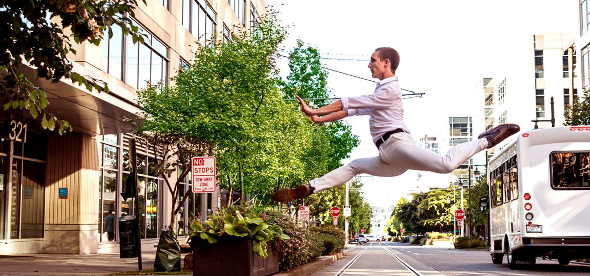 Male dancer leaping over streetcar tracks.