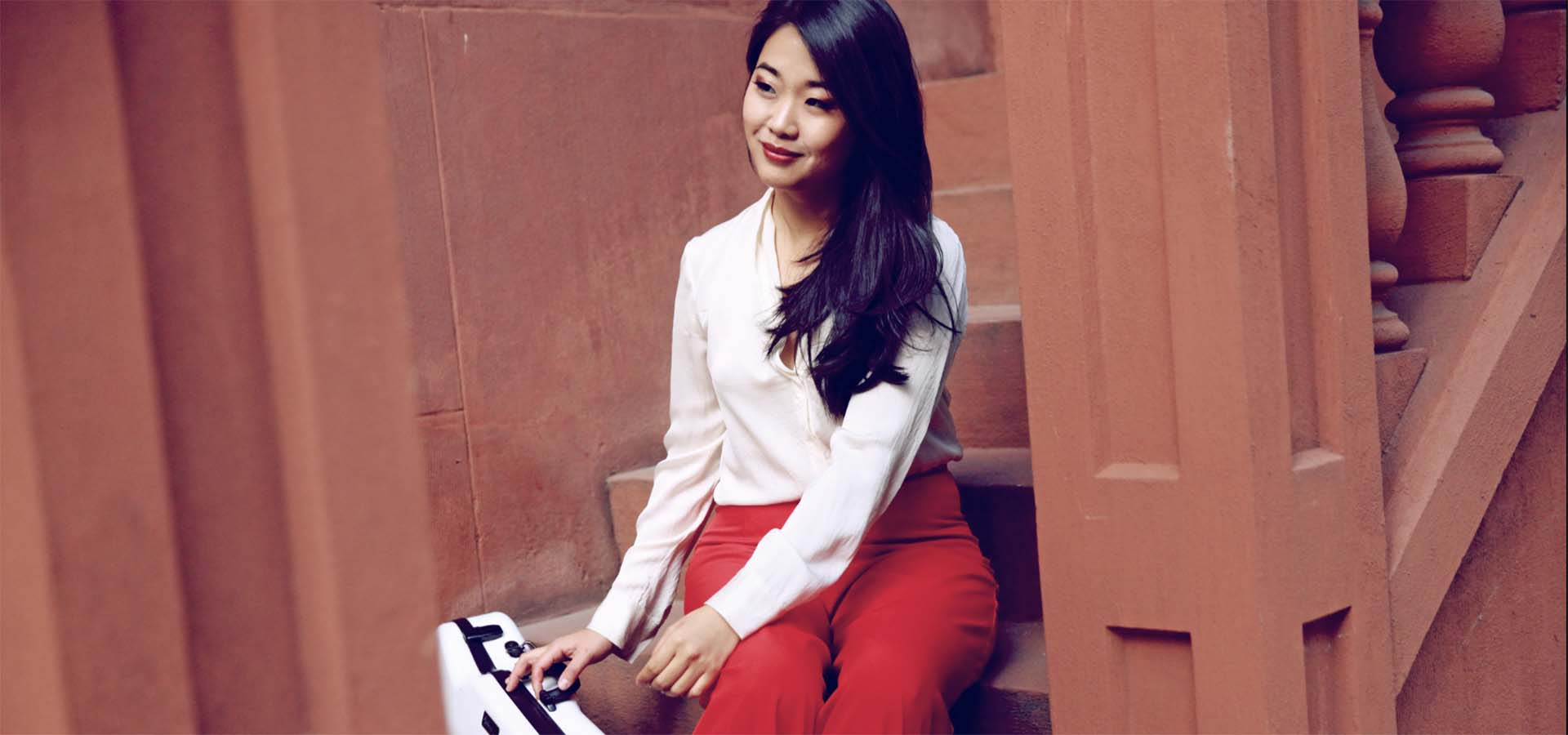 Asian-American woman with white shirt and red pants holding a violin case