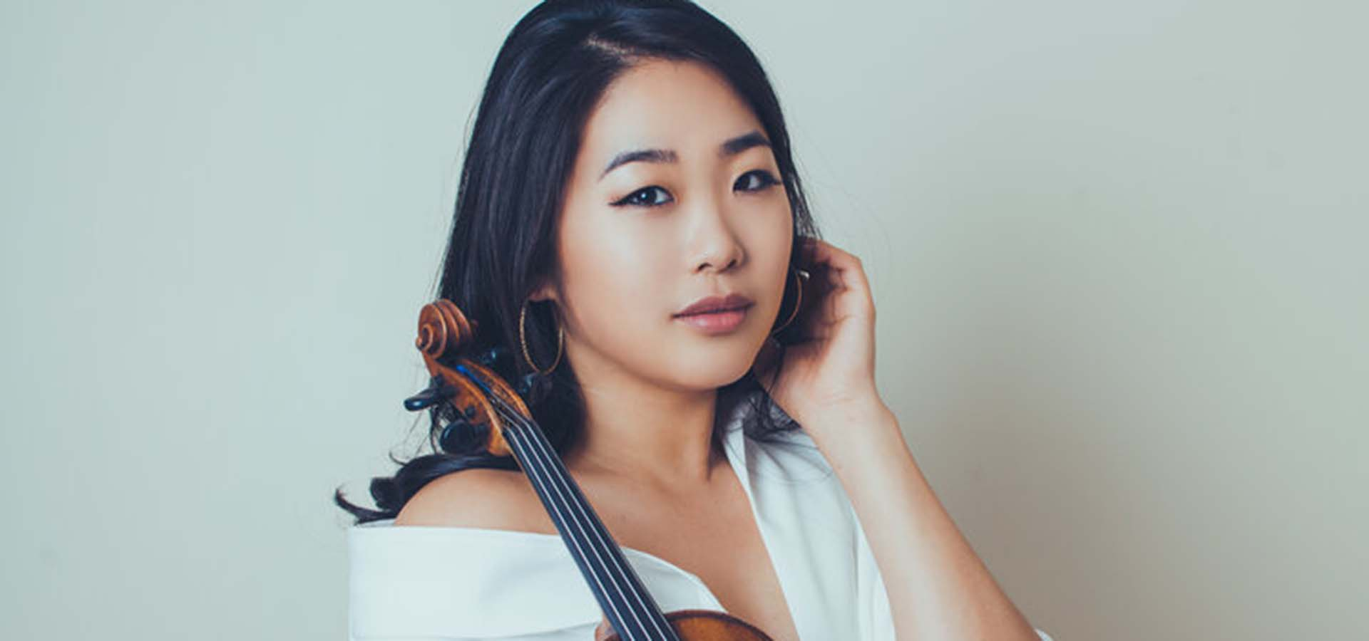 Asian women dressed in white holding a violin