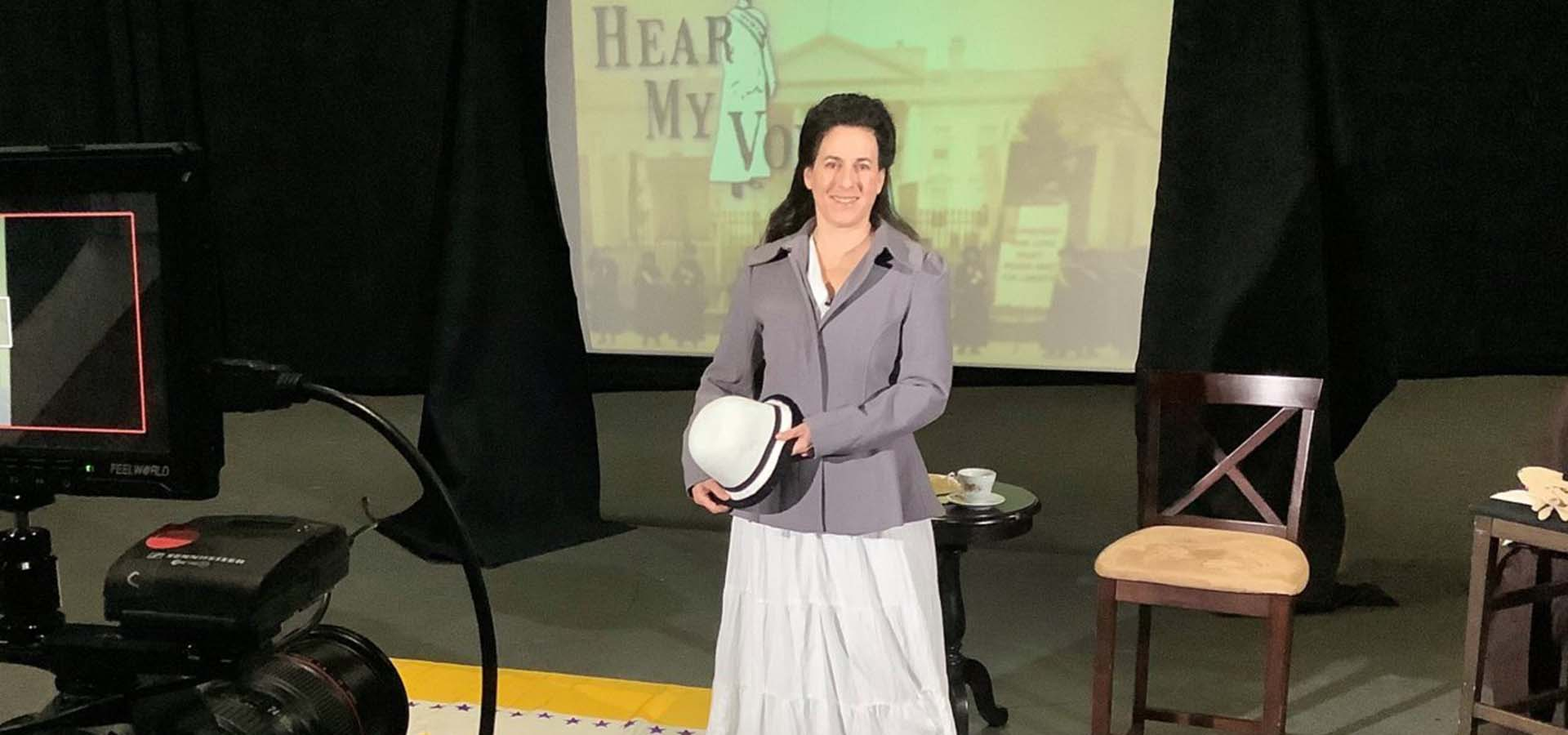 Women presenter in classroom setting holding a white hat
