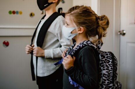School-aged girl and boy with backpacks and masks on, appear ready to head off to school.
