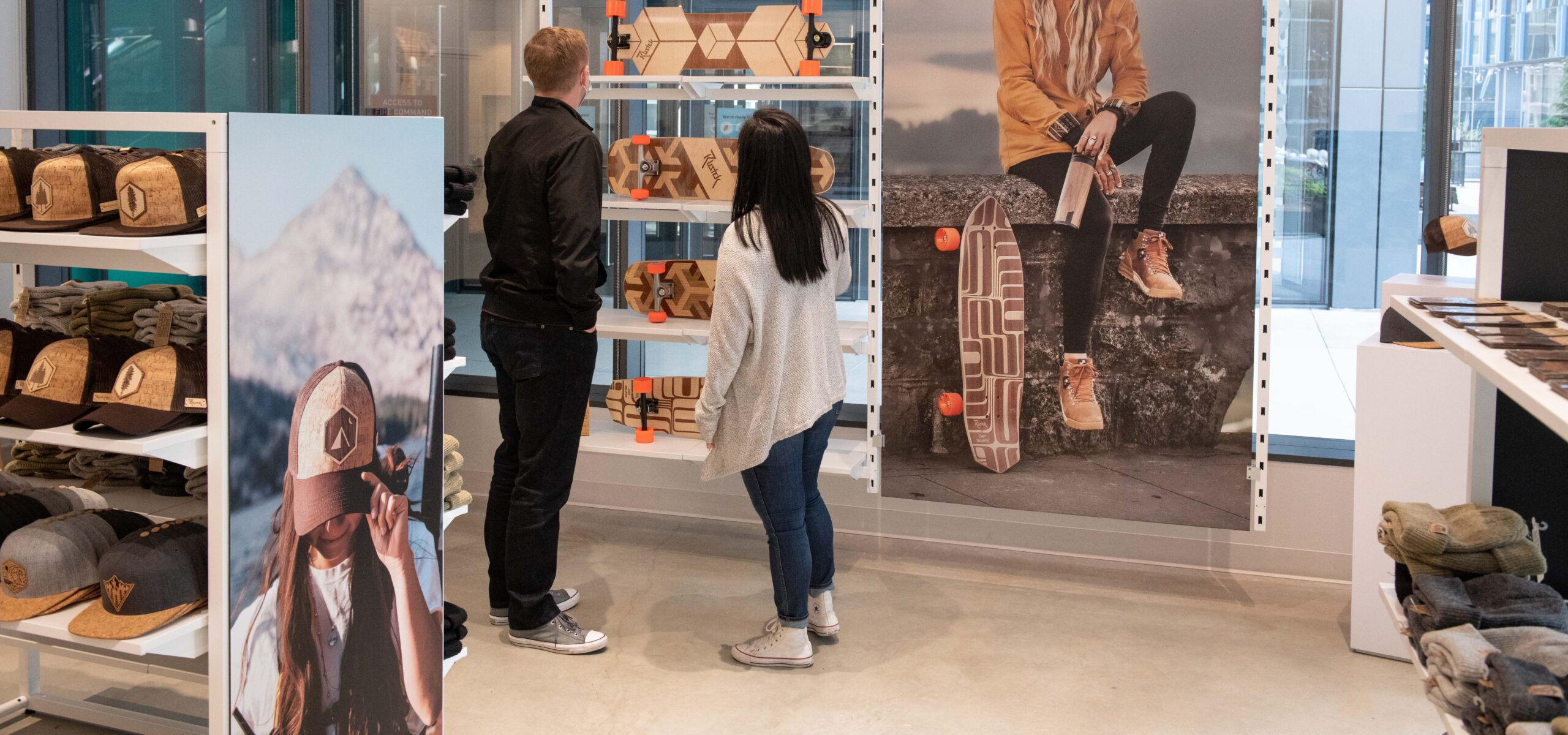 Man and woman looking at wooden skateboards in a store.