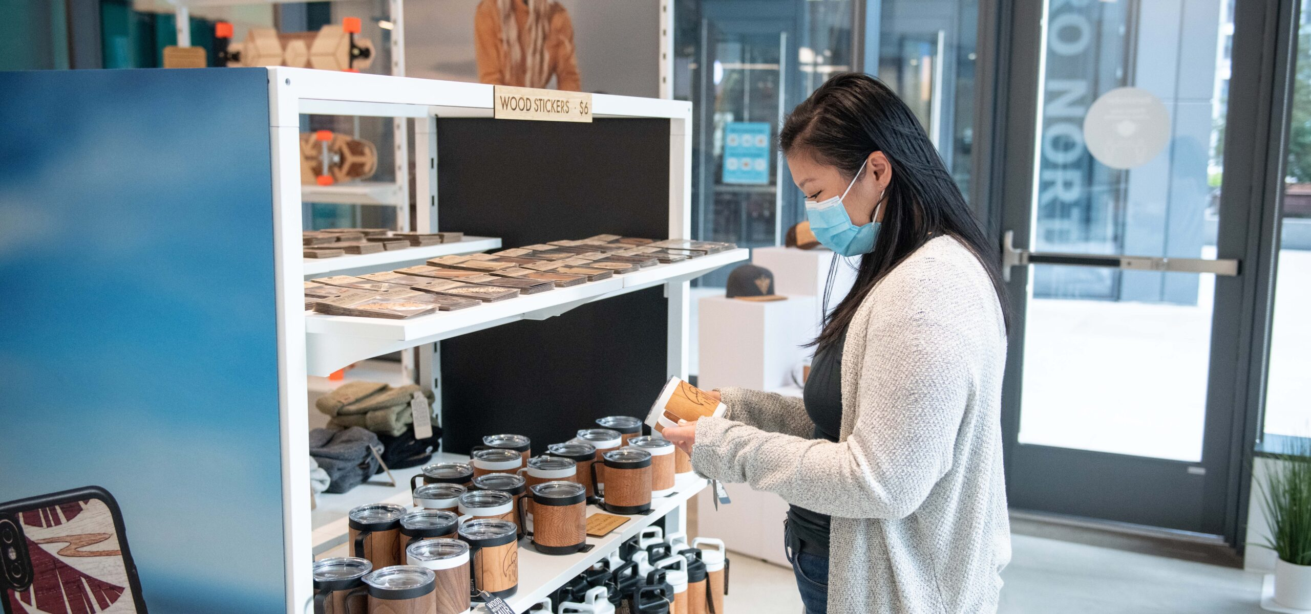 Woman looking at wooden handmade phone cases and tumblers.