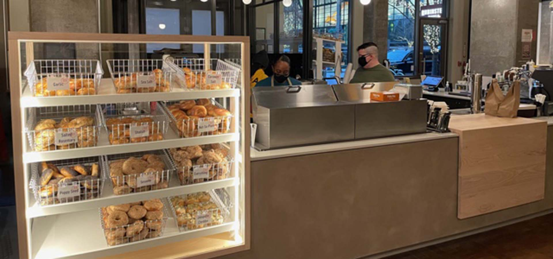 Store interior of a bagel counter with staff and baskets of bagels.