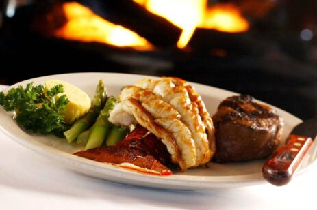 Surf and turf plated meal in front of a fireplace.