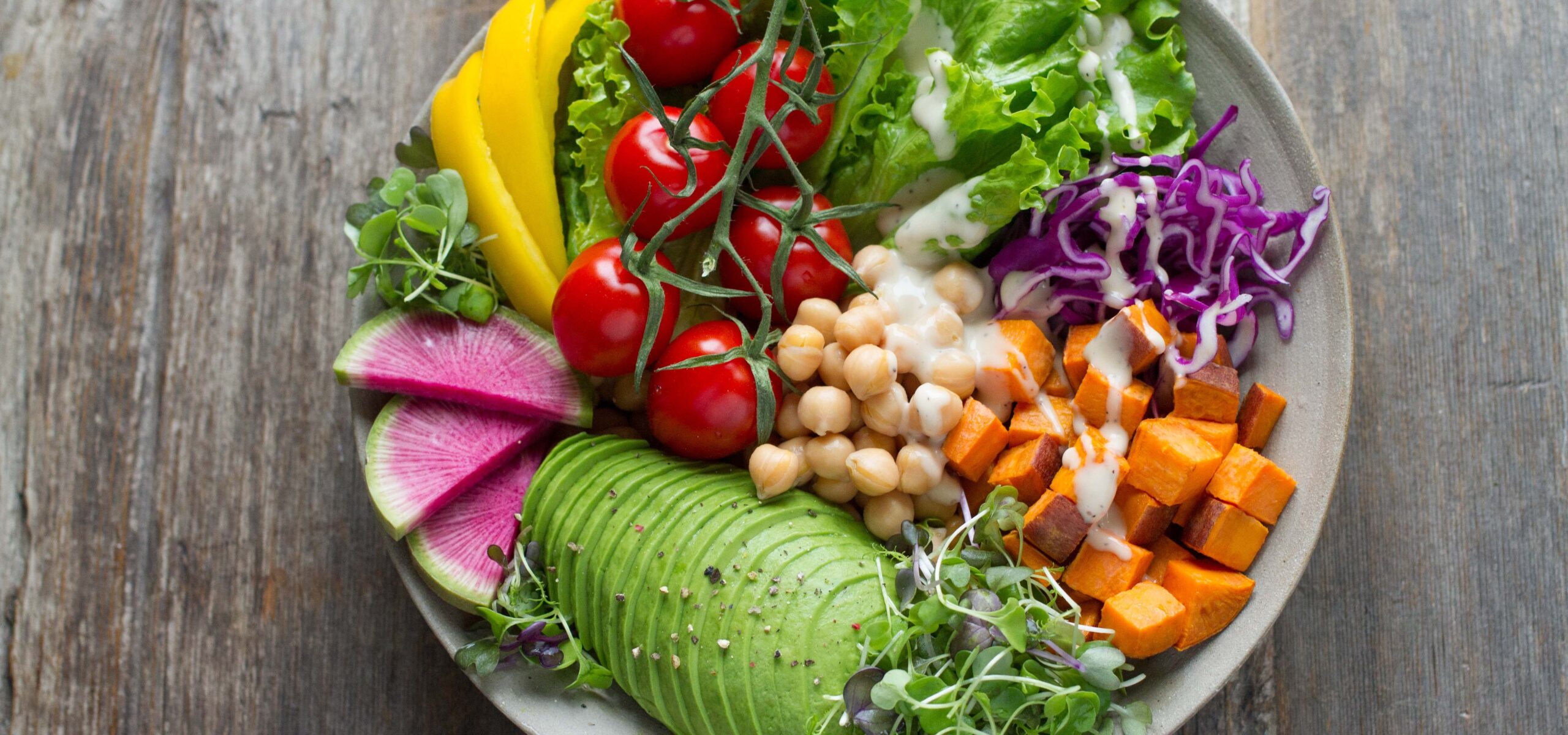 White bowl with colorful salad items such as carrots, tomatoes, and avocados.