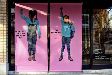 Window mural art featuring an African-American girl with messaging about BIPOC awareness.