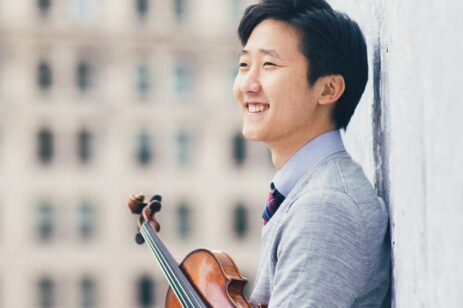 Asian American violinist, Sean Lee smiling and holding his violin.