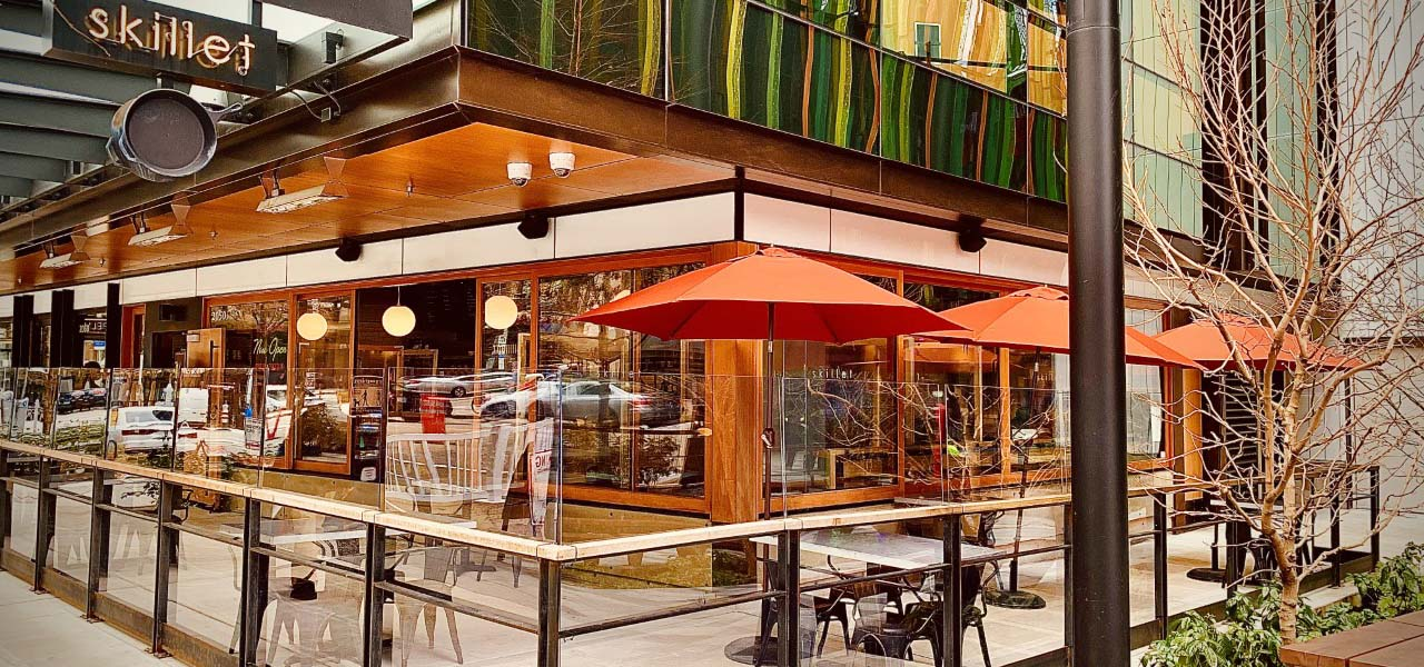 Photograph of restaurant outdoor patio with bright orange umbrellas over tables.