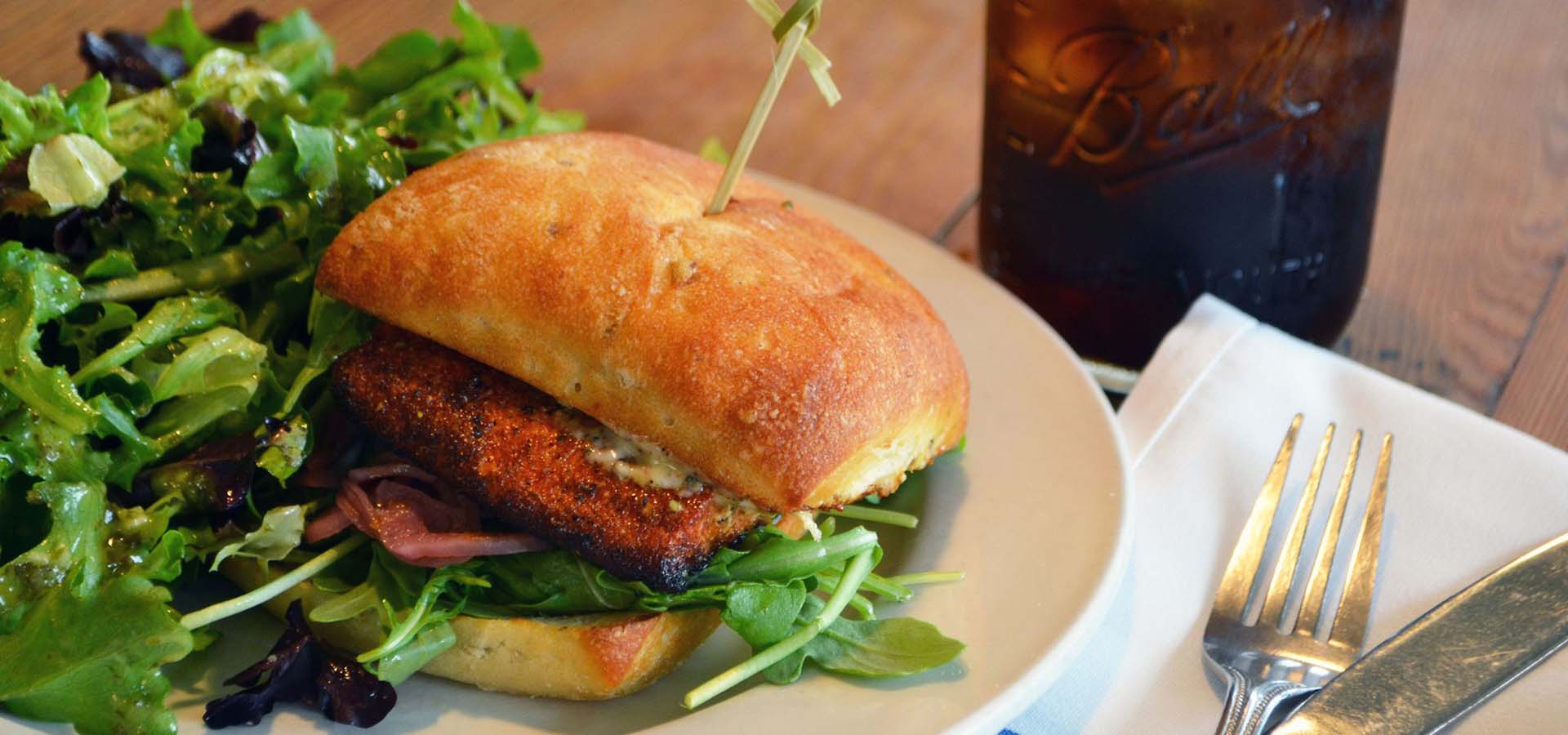Grilled salmon sandwich with greens on a plate.