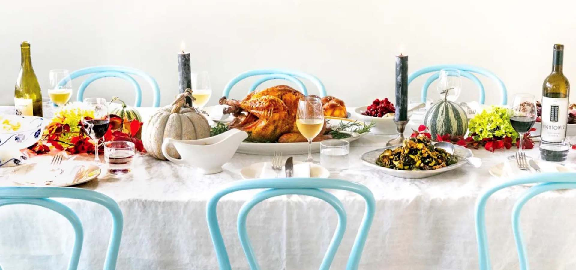 Thanksgiving table with turkey, sides, on a white table cloth.