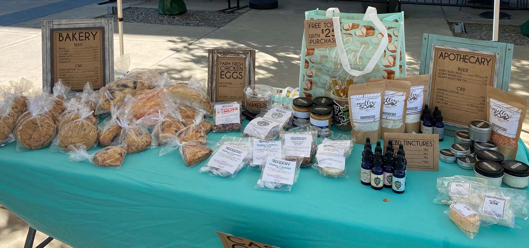 Table at a farmer's market filled with baked goods.