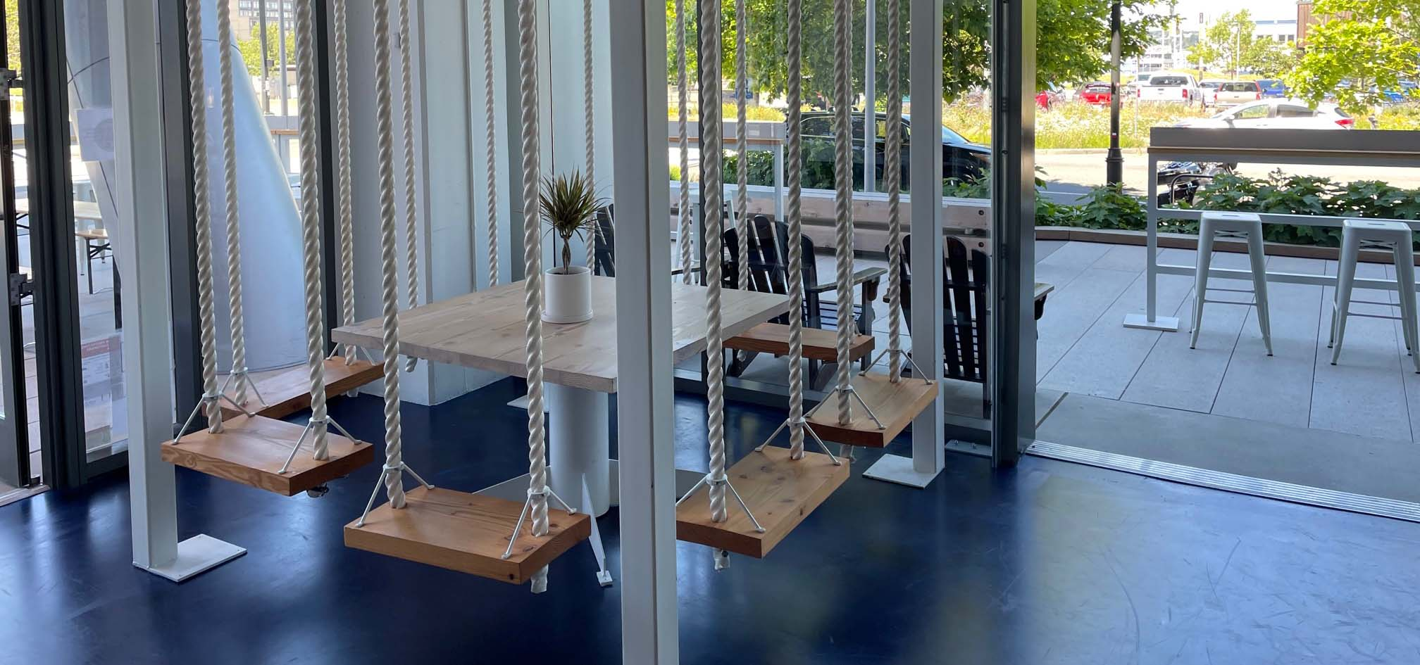 Treehouse swings inside a restaurant for fun patron seating.