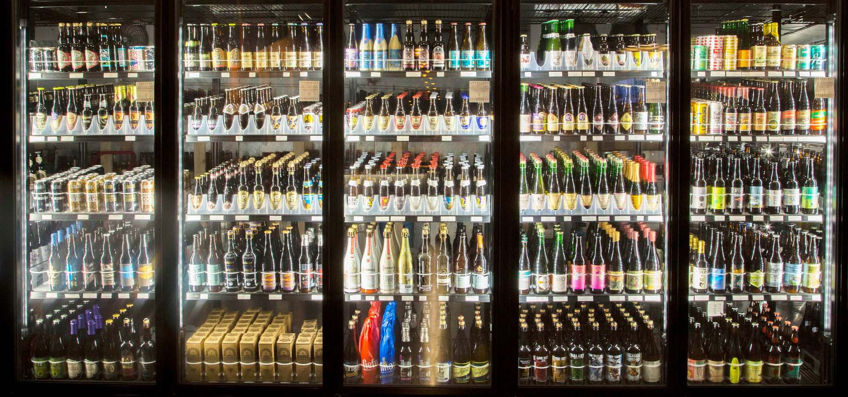 Grocery coolers filled with selections of beer.