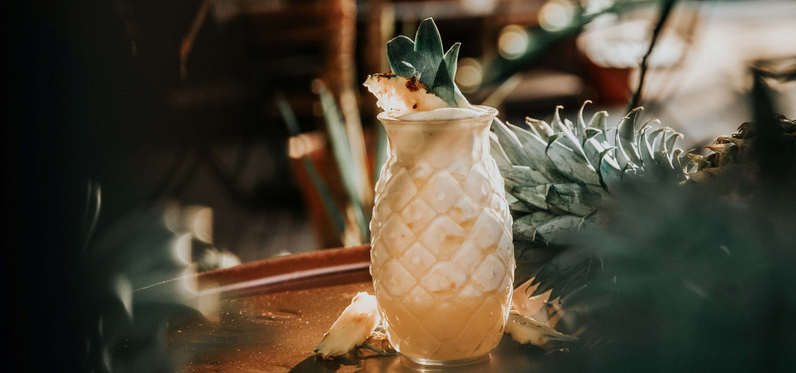 Cocktail in a pineapple shaped glass on a bar top.