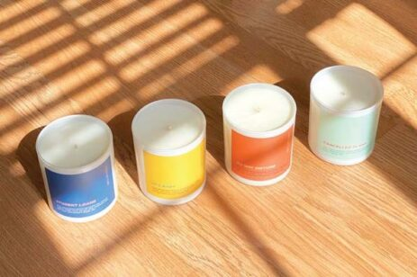 Four candles in a row on a floor with shadows and light.