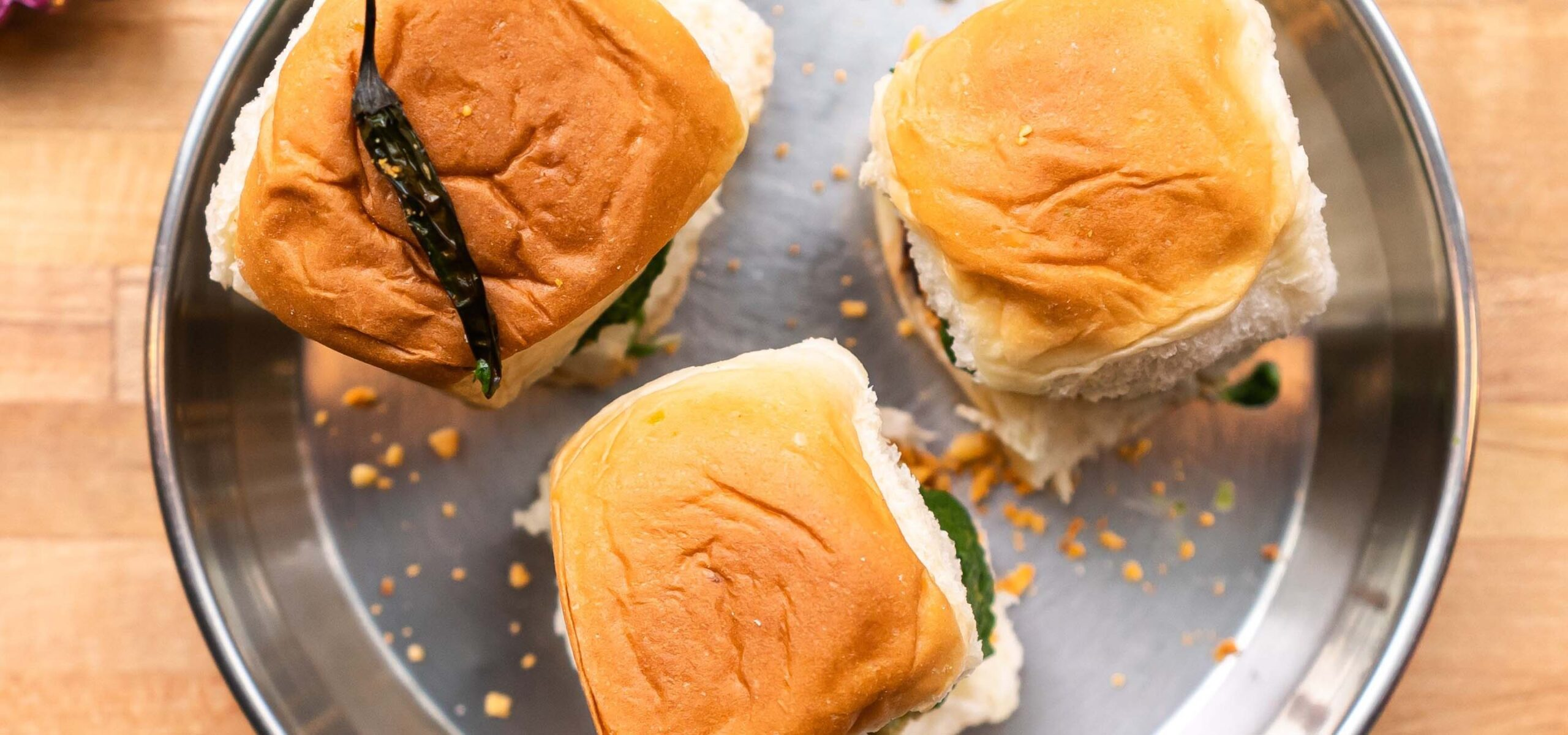 Three Vada Pav sliders on a metal dish; one topped with a roasted green chili pepper.