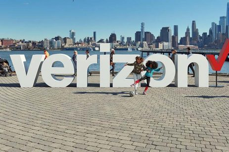 People playing on a waterfront with the Verizon logo installed as public art on the ground